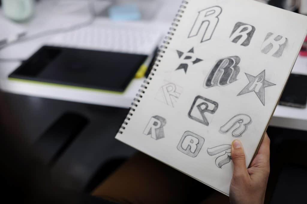 Hand Holding Notebook With Drew Brand Logo Creative Design Ideas