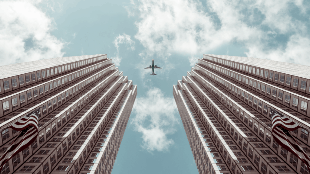 Plane flies between two tall business buildings